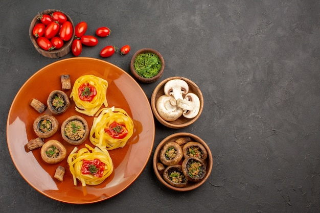 Vista superior saborosos cogumelos cozidos com vegetais em fundo escuro