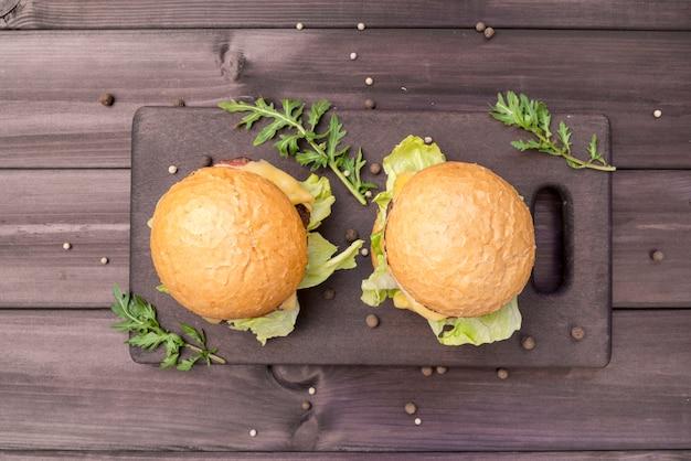 Vista superior saborosos hambúrgueres na mesa de madeira