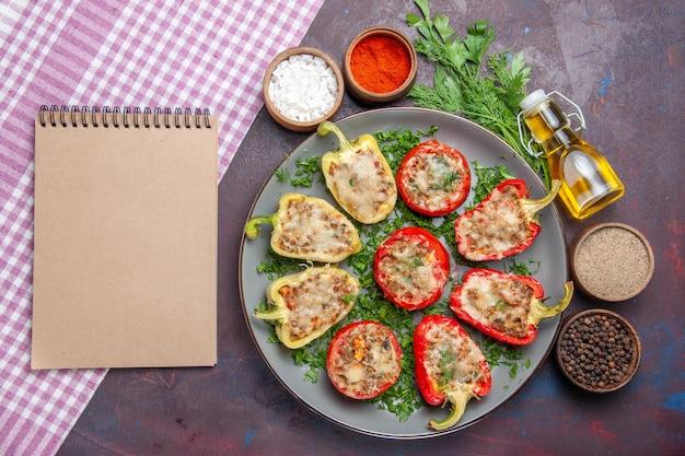Vista superior saborosos pimentões deliciosa refeição cozida com carne e verduras na superfície escura jantar prato pimenta comida picante Foto gratuita