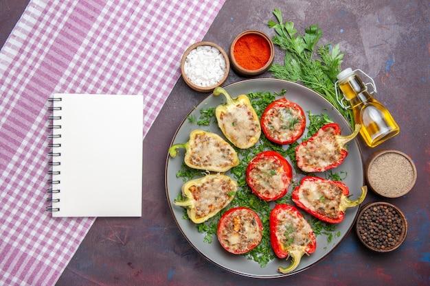 Vista superior saborosos pimentões deliciosa refeição cozida com carne e verduras na superfície escura jantar prato pimenta comida picante