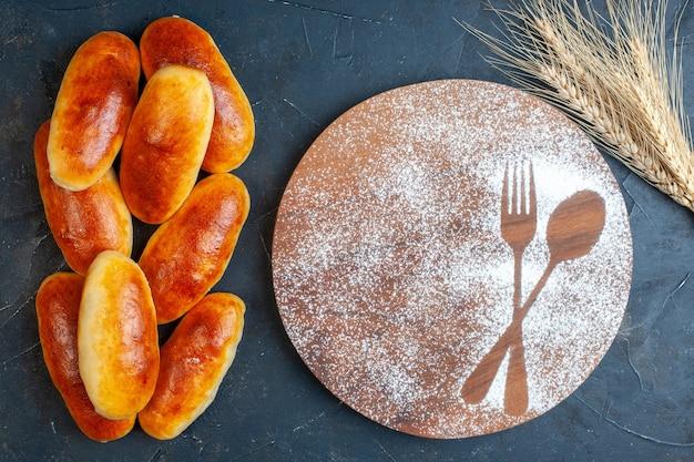 Vista superior saborosos rolos de jantar com impressão de garfo e colher em açúcar de confeiteiro na placa de madeira