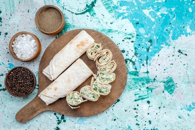 Vista superior saborosos rolos de vegetais inteiros e fatiados com verduras e temperos no fundo azul do rolo de refeição alimentar de cor vegetal