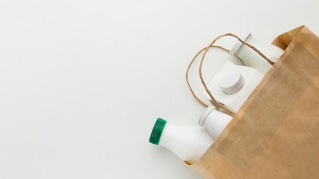 Vista superior saco de papel com garrafas de leite