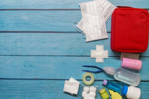 Vista superior, saco de primeiros socorros garoto com suprimentos médicos em madeira