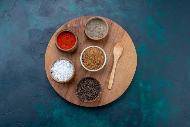Vista superior sal e pimenta com outros temperos na superfície azul escura da mesa de ingredientes de pimenta