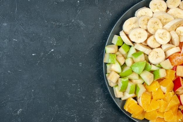Vista superior salada de frutas frescas fatiadas bananas, maçãs e laranjas em fundo escuro