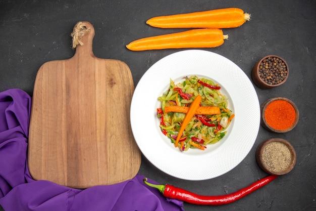 Vista superior salada de legumes, tábua de cortar especiarias, cenoura, toalha de mesa roxa