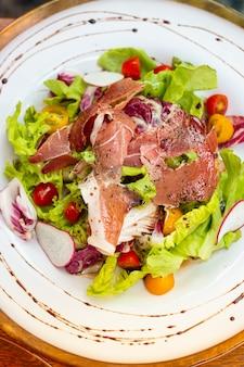 Vista superior salada de pato defumado em chapa branca em cima da mesa