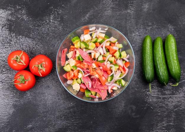 Vista superior salada de pepino picada na tigela de vidro com tomate e legumes frescos em pedra preta