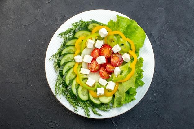 Vista superior salada de vegetais consiste em fatias de pepino, tomate pimenta e queijo em fundo escuro