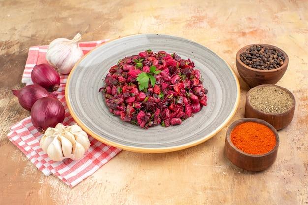 Vista superior salada de vegetais saudável em um prato de cerâmica com pimenta preta, cúrcuma, pimenta preta moída à direita e três cebolas vermelhas de alho à esquerda em uma mesa de madeira