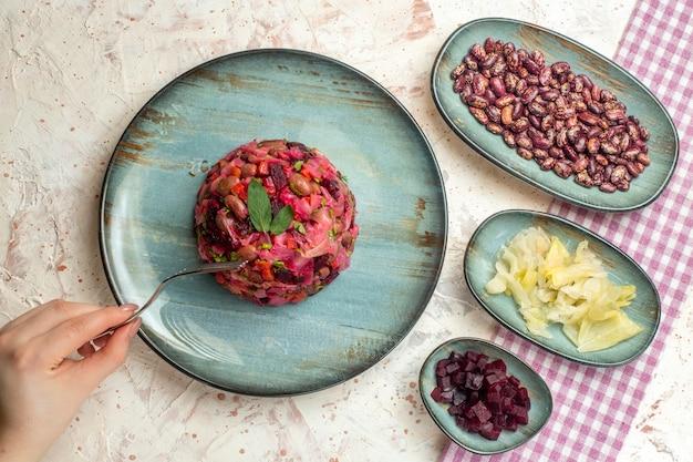Vista superior salada de vinagrete em prato redondo repolho em conserva feijão cortado beterraba no garfo de prato em mão feminina em mesa cinza claro