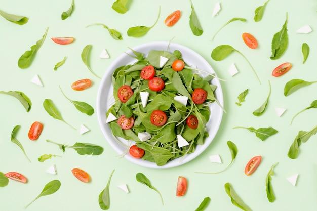 Vista superior salada fresca com tomate em cima da mesa