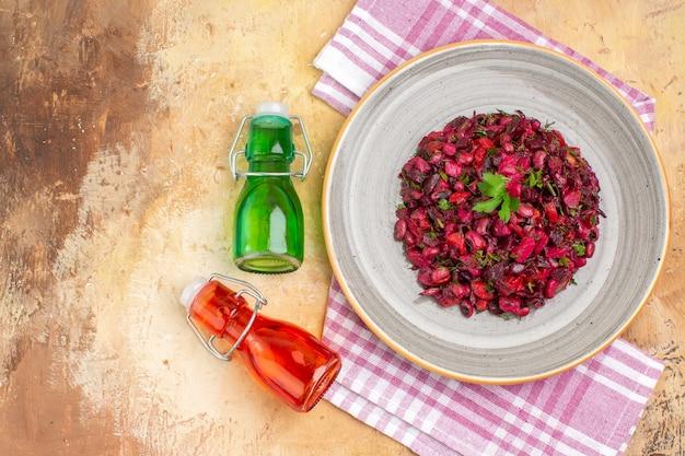 Vista superior salada requintada em um prato de cerâmica com garrafas de óleo atraentes e toalha xadrez roxa