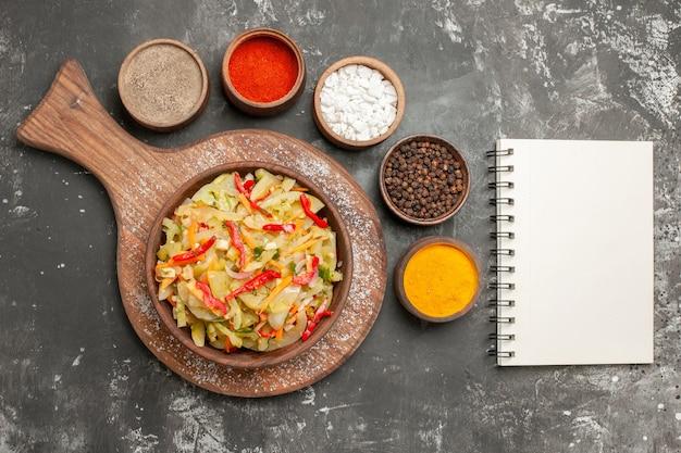 Vista superior salada salada no quadro caderno branco de especiarias coloridas