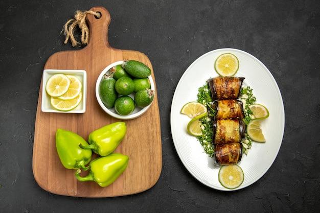 Vista superior salgados rolinhos de berinjela com rodelas de limão em uma superfície cinza escura