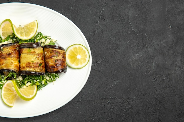 Vista superior salgados rolos de berinjela com rodelas de limão em frutas escuras na superfície cozinhando o prato do jantar