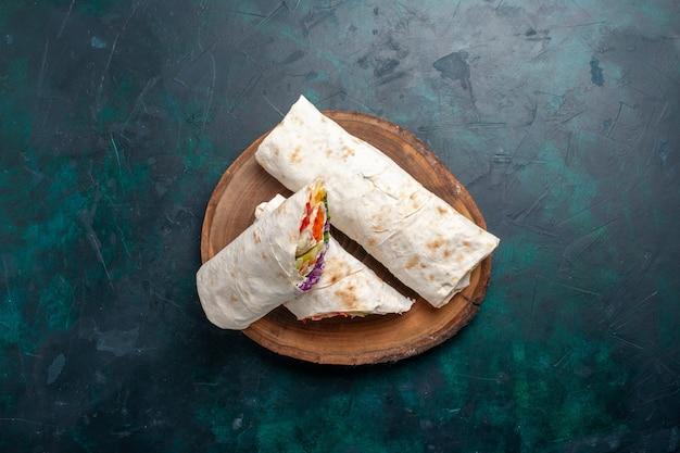 Vista superior sanduíche de carne um sanduíche feito de carne grelhada no espeto com vegetais no azul escuro mesa sanduíche hambúrguer comida refeição almoço carne foto