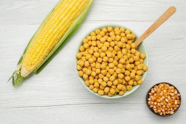 Vista superior sementes de milho amarelo colorido com cereais dentro da placa em branco