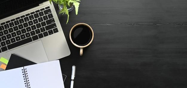 Vista superior simples do equipamento de escritório a montar na mesa preta. computador portátil, xícara de café, caderno, post-it, caneta e vaso de plantas. conceito de mesa de trabalho moderno.