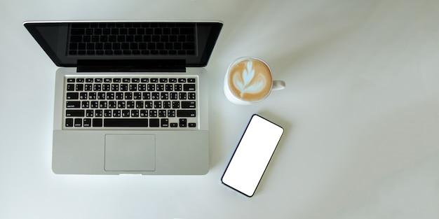 Vista superior simulada smartphone com laptop de computador mouse e xícara de café. espaço de cópia plana leigo.