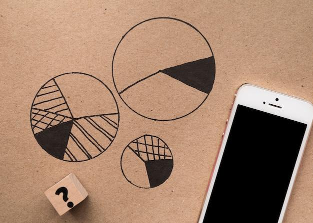 Vista superior smartphone ao lado de gráficos