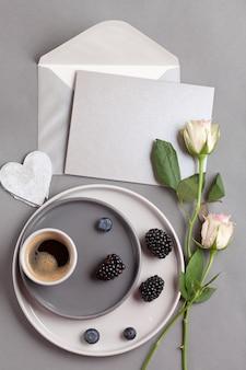Vista superior sobre a xícara de café e cinza cartão postal com envelope