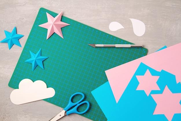 Vista superior sobre ferramentas de corte de papel, tesoura, cortador, tapete de corte e objetos de papel criados. conceito de projeto moderno de diy