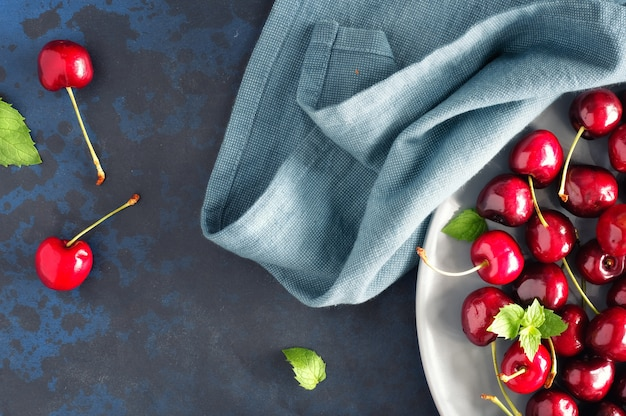 Vista superior sobre o prato cinzento de cerejas no fundo escuro