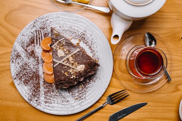 Vista superior sobremesa bolo de chocolate com fatias de tangerina e um copo de chá
