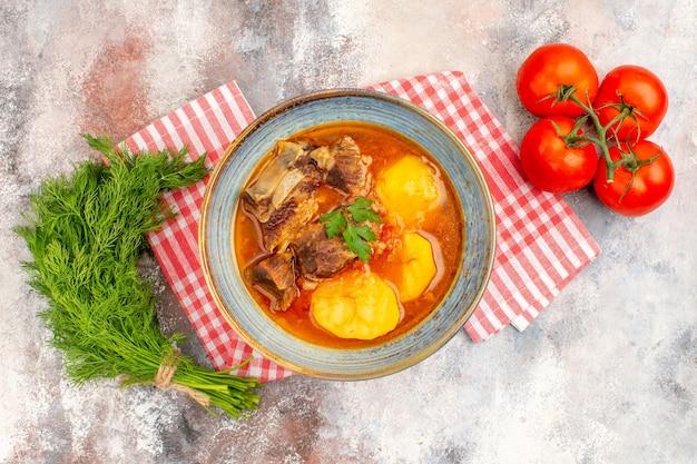 Vista superior, sopa bozbash caseira, toalha de cozinha, um monte de tomates de endro em um fundo nu