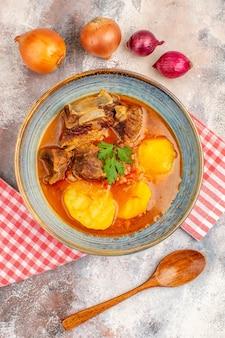 Vista superior sopa bozbash com colher de pau cebola amarela e vermelha em fundo nude
