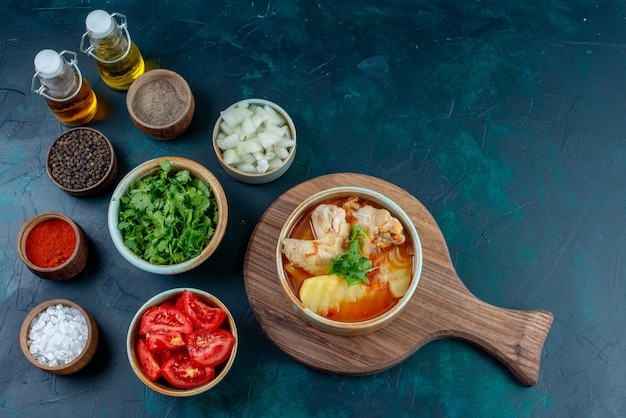 Vista superior sopa de galinha com batatas junto com sal pimenta legumes frescos e óleo na mesa azul escuro sopa carne comida jantar refeição