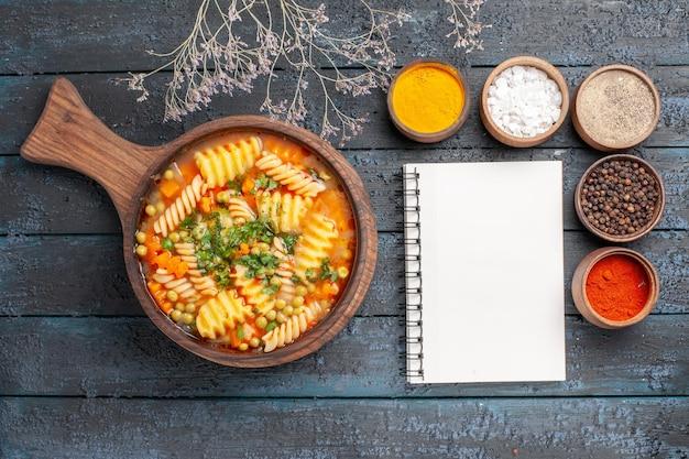 Vista superior sopa de massa em espiral refeição deliciosa com diferentes temperos na mesa escura sopa cor prato de massa italiana culinária