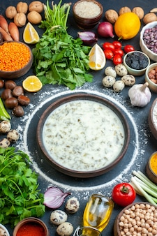 Vista superior sopa dovga tomate salsa óleo garrafa ovos cebola verde arroz em uma tigela na mesa