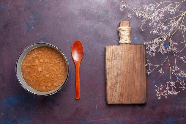 Vista superior sopa marrom dentro do prato na superfície escura sopa refeição de vegetais alimentos óleo de cozinha