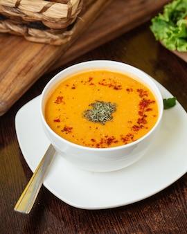 Vista superior sopa quente com hortelã seca dentro de um prato branco sobre a mesa de madeira comida sopa refeição