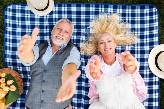Vista superior, sorrindo casal com as mãos levantadas