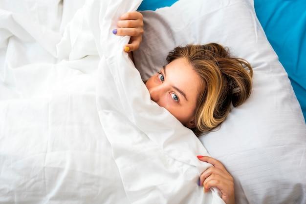 Vista superior, sorrindo, mulher puxando o lençol debaixo do nariz