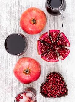 Vista superior suco de romã e sementes de romã no prato em forma de coração na mesa de madeira branca