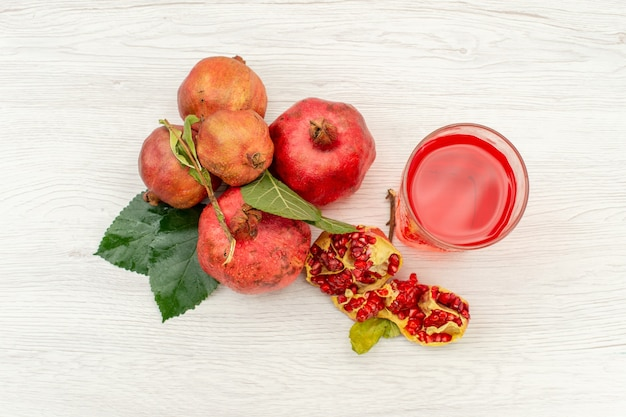 Vista superior suco de romã fresco com romãs frescas na superfície branca suco de fruta cor de bebida