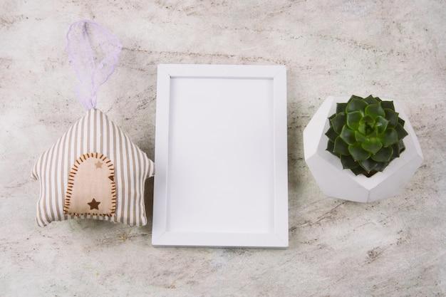 Vista superior suculenta em pote de concreto, casa de brinquedo de pelúcia e mock up quadro branco sobre uma mesa de mármore