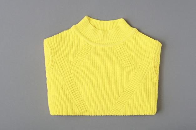 Vista superior suéter amarelo quente estampado em malha em fundo cinza
