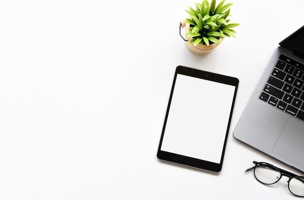 Vista superior tablet, caneta, óculos e laptop na mesa de escritório