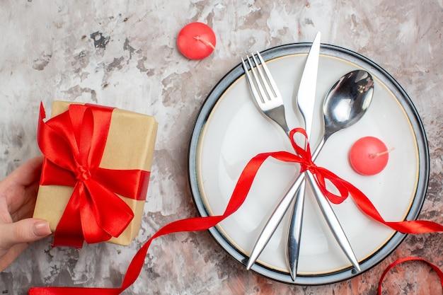 Vista superior, talheres de prata, colher, garfo e faca com laço vermelho e presentes sobre uma superfície leve