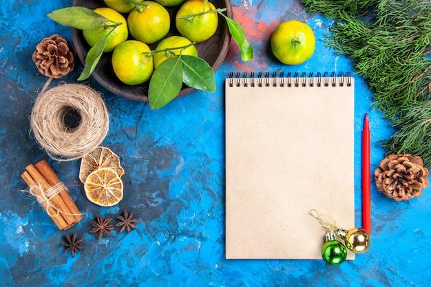 Vista superior tangerinas amarelas com folhas em uma tigela de madeira bloco de notas lápis vermelho enfeites de natal canela paus de anis na superfície azul