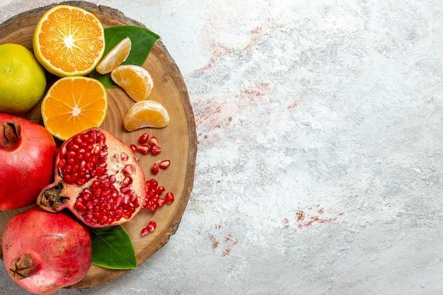 Vista superior tangerinas e romãs frutas frescas maduras no fundo branco frutas cor da árvore saúde fresco