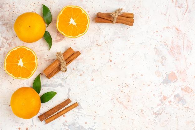 Vista superior tangerinas frescas cortadas em paus de canela em uma superfície brilhante e isolada com espaço livre