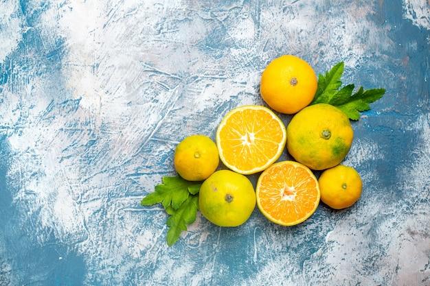 Vista superior tangerinas frescas cortadas em superfície azul e branca com espaço de cópia