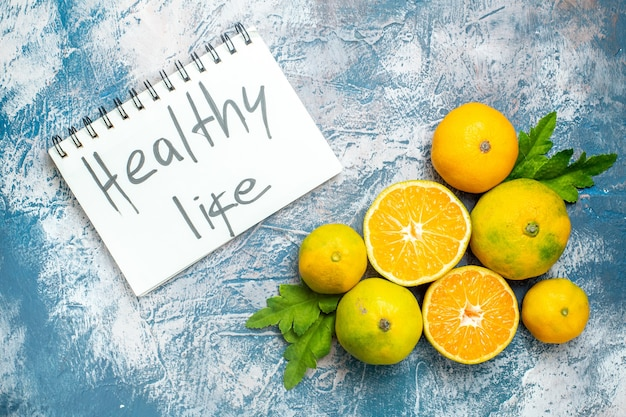 Vista superior tangerinas frescas cortadas tangerinas vida saudável escrita no bloco de notas na superfície branca e azul